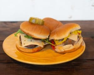 three sliders on a plate with various toppings